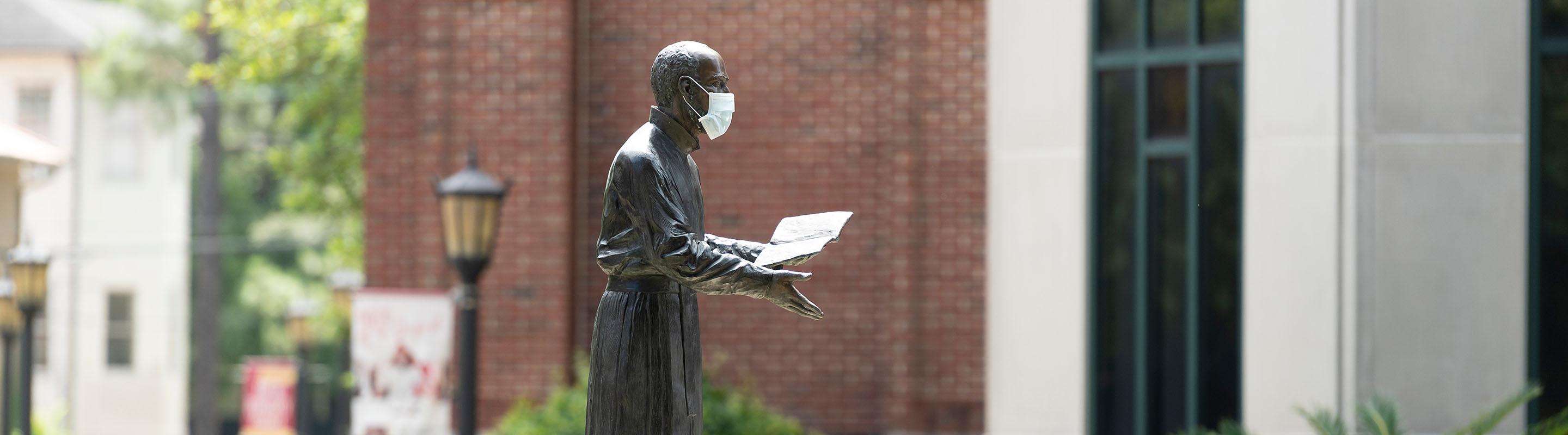 St. Ignatius statue with face mask